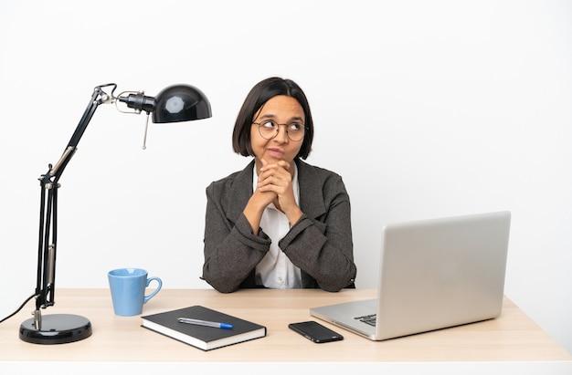 사무실에서 일하는 젊은 비즈니스 혼혈 여자는 의심을 가지고 혼란스러운 얼굴 표정으로