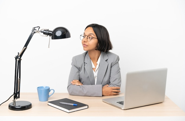 측면을 보는 동안 의심을 갖는 사무실에서 일하는 젊은 비즈니스 혼혈 여자