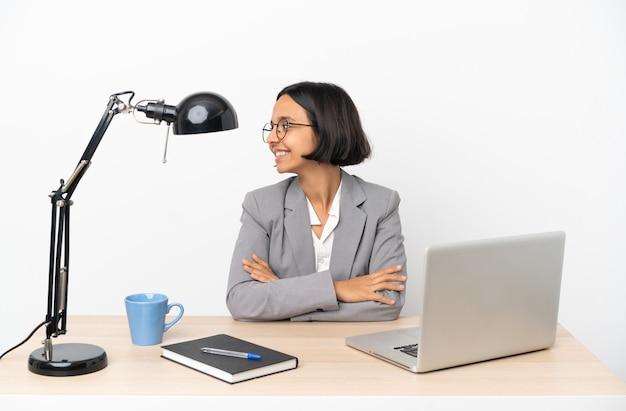 横位置でオフィスで働く若いビジネス混血女性