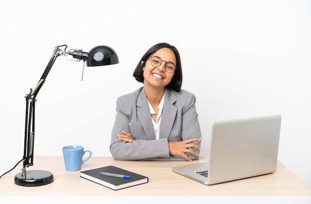 正面の位置で腕を組んだままオフィスで働く若いビジネス混血女性
