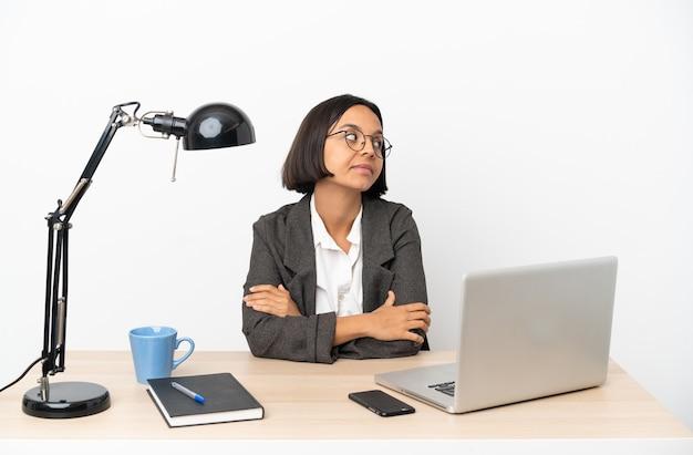 腕を組んでオフィスで働く若いビジネス混血女性