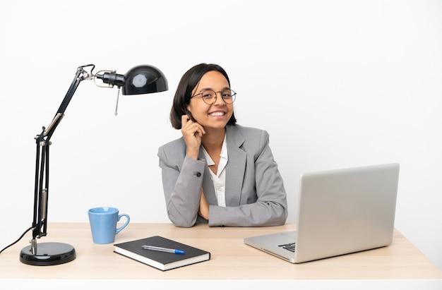 笑いながらオフィスで働く若いビジネス混血女性