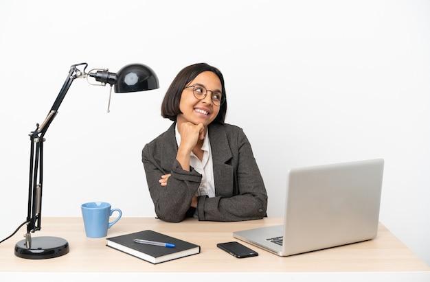 Молодой бизнес смешанной расы женщина, работающая в офисе, глядя вверх, улыбаясь