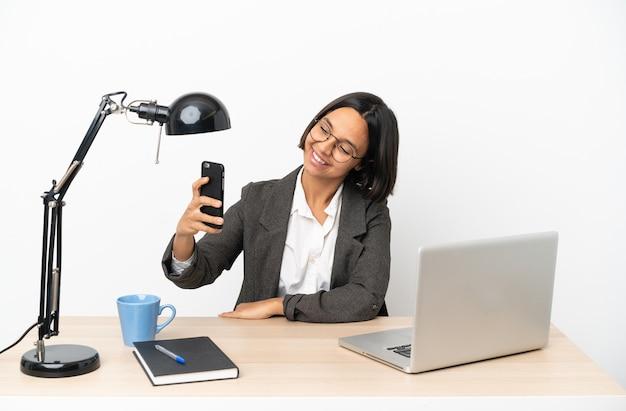 Молодая деловая женщина смешанной расы, работающая в офисе, делает селфи