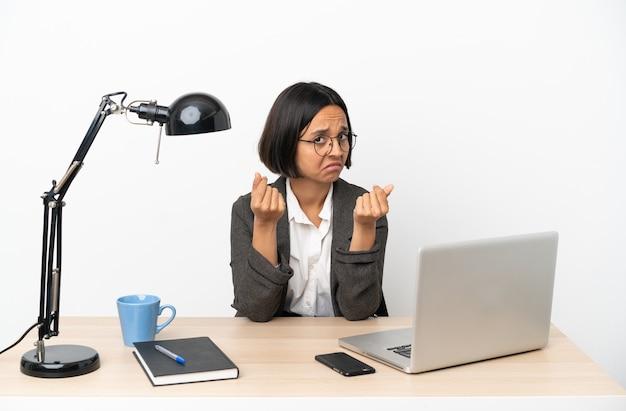 Молодая деловая женщина смешанной расы, работающая в офисе, делает денежный жест, но разрушена