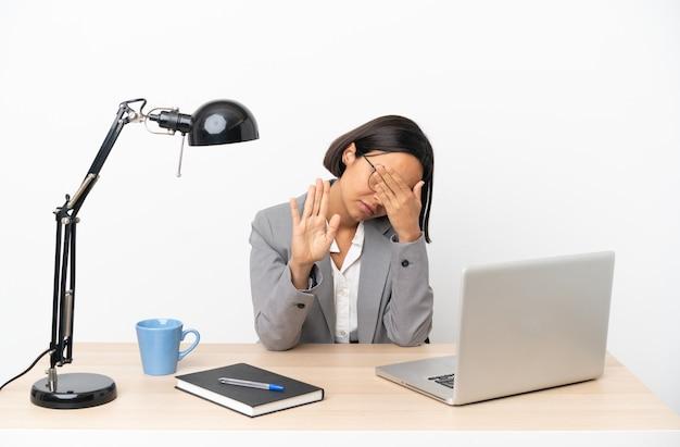 중지 제스처를 만들고 얼굴을 덮고 사무실에서 일하는 젊은 비즈니스 혼혈 여자
