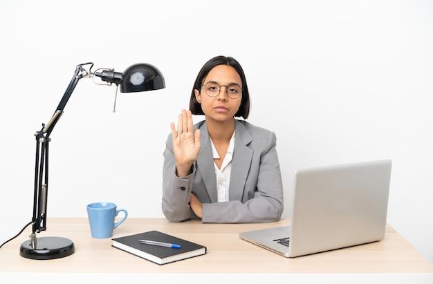 중지 제스처를 만드는 사무실에서 일하는 젊은 비즈니스 혼혈 여자