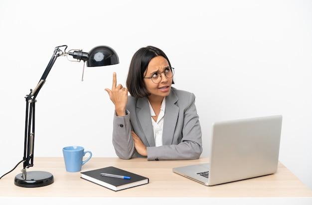 Молодая деловая женщина смешанной расы, работающая в офисе, делает жест безумия, положив палец на голову
