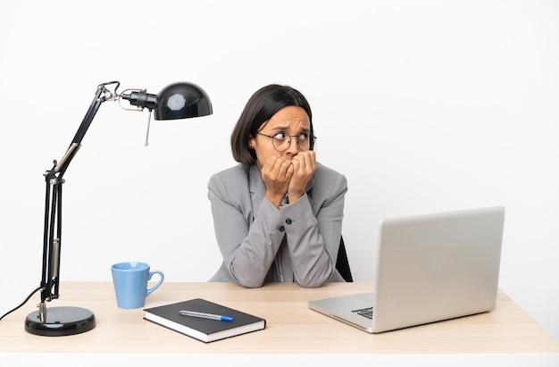 Молодая деловая женщина смешанной расы, работающая в офисе, нервничает и испугалась, прикладывая руки ко рту
