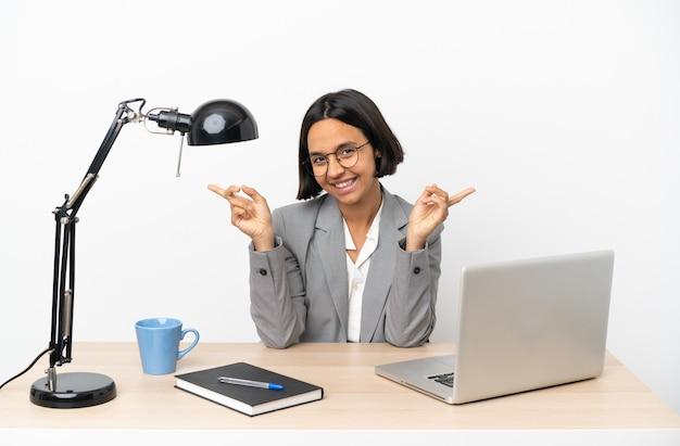 Молодая деловая женщина смешанной расы, работающая в офисе, указывая пальцем на боковые стороны и счастливая