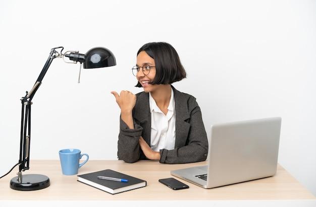 製品を提示する側を指しているオフィスで働く若いビジネス混血の女性