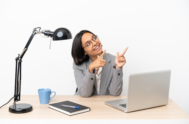 좋은 아이디어를 가리키는 사무실에서 일하는 젊은 비즈니스 혼혈 여자