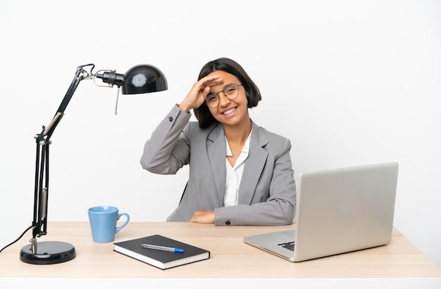 행복한 표정으로 손으로 경례하는 사무실에서 일하는 젊은 비즈니스 혼혈 여성