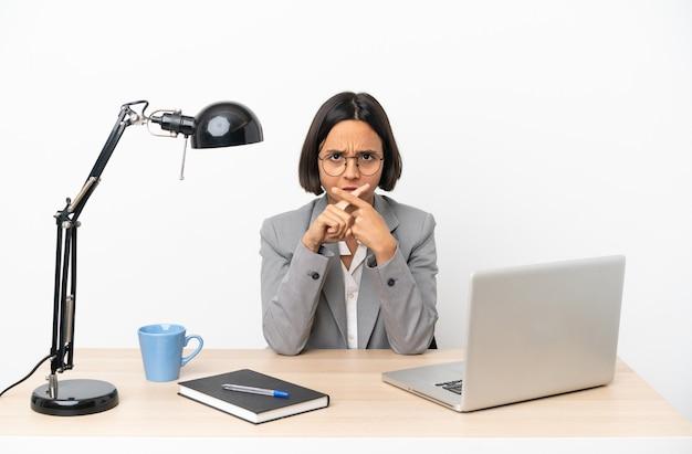 Молодая деловая женщина смешанной расы, работающая в офисе, показывает знак жеста молчания