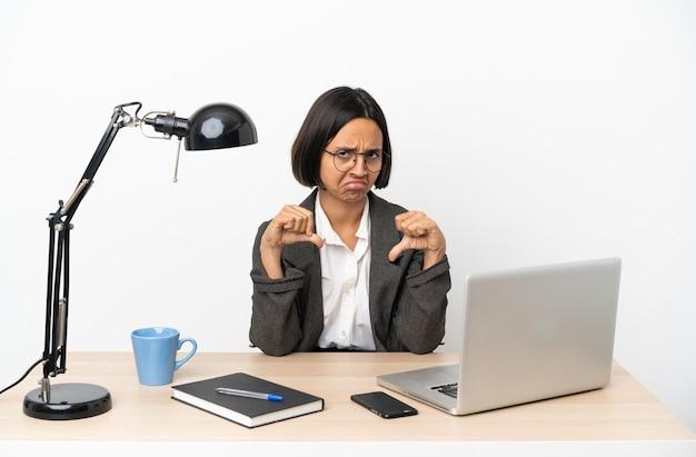 両手で親指を下に見せるオフィスで働く若いビジネス混血女性