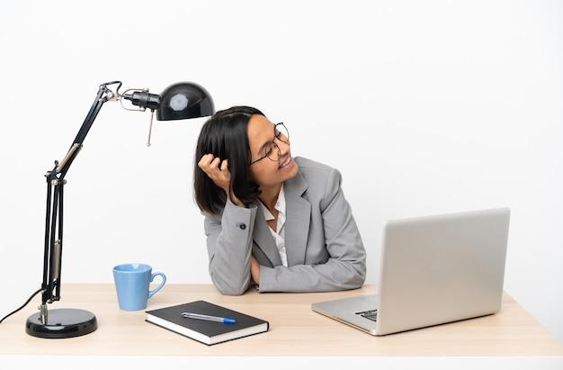 많이 웃 고 사무실에서 일하는 젊은 비즈니스 혼혈 여자