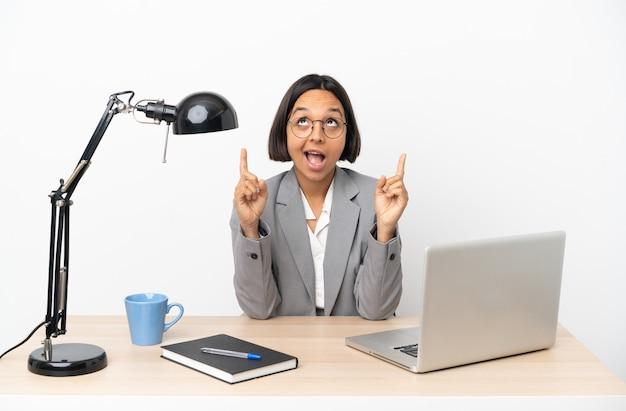 Молодая деловая женщина смешанной расы, работающая в офисе, удивлена и указывает вверх