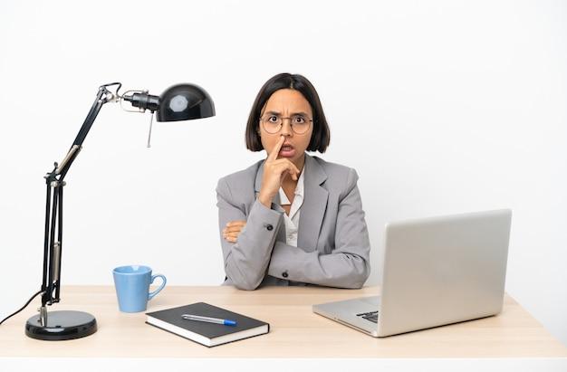 Молодая деловая женщина смешанной расы, работающая в офисе, удивлена и шокирована, глядя вправо