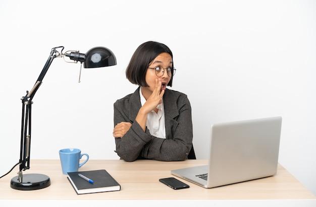 Молодая деловая женщина смешанной расы, работающая в офисе, шепчет что-то с удивленным жестом, глядя в сторону