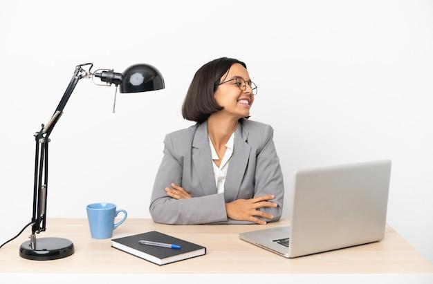 Молодая деловая женщина смешанной расы, работающая в офисе со скрещенными руками и счастливыми