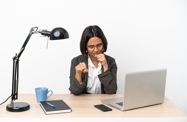 戦うジェスチャーでオフィスで働く若いビジネス混血女性