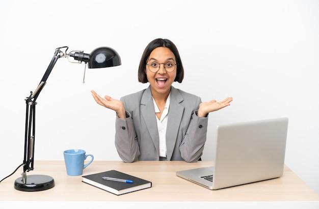 ショックを受けた表情でオフィスで働く若いビジネス混血女性