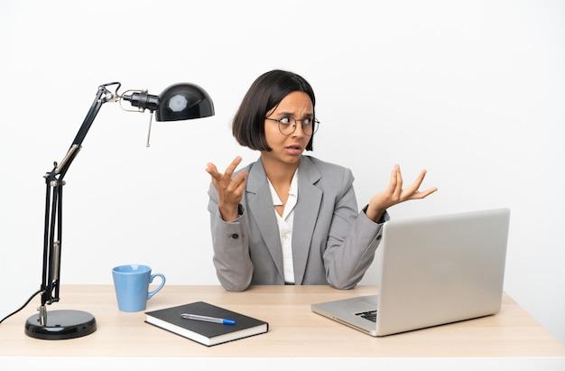 Молодая деловая женщина смешанной расы, работающая в офисе с удивленным выражением лица, глядя в сторону