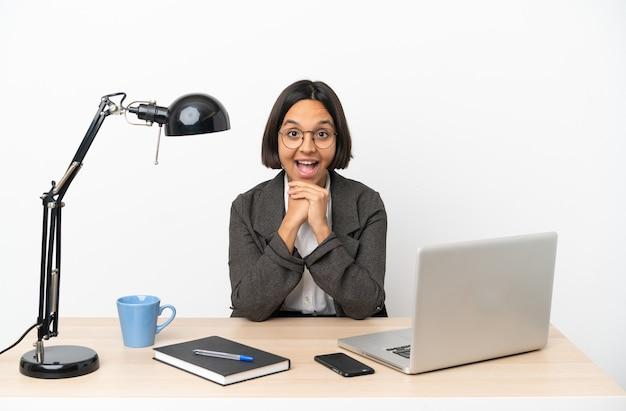 Молодая деловая женщина смешанной расы, работающая в офисе с удивленным выражением лица