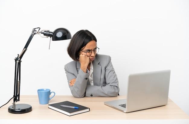 Молодая деловая женщина смешанной расы, работающая в офисе с усталым и скучающим выражением лица