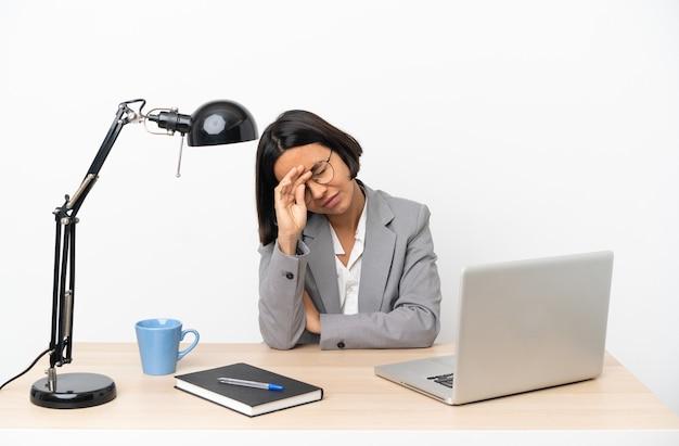 疲れて病気の表情でオフィスで働く若いビジネス混血女性