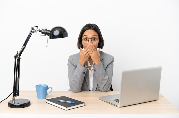 Young business mixed race woman working at office covering mouth with hands