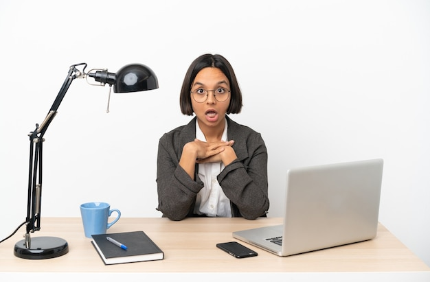 Young business mixed race woman working at office surprised and shocked while looking right
