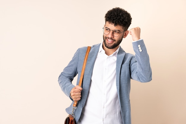 Young business moroccan man isolated on beige background celebrating a victory