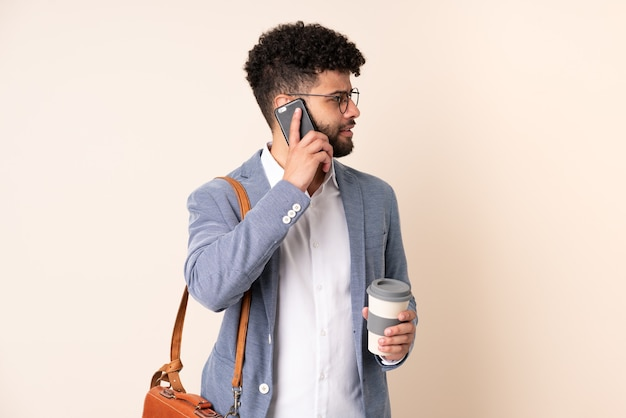 Young business moroccan man isolated on beige background holding coffee to take away and a mobile