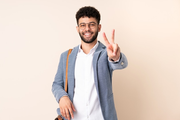 Young business moroccan man isolated on beige smiling and showing victory sign
