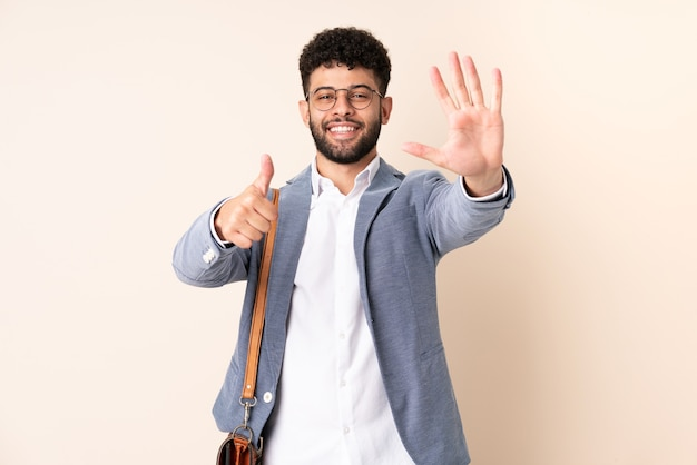 Young business moroccan man isolated on beige wall counting six with fingers