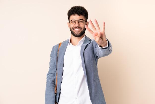 Молодой деловой марокканский мужчина изолирован на бежевом фоне счастливым и считает четыре пальцами