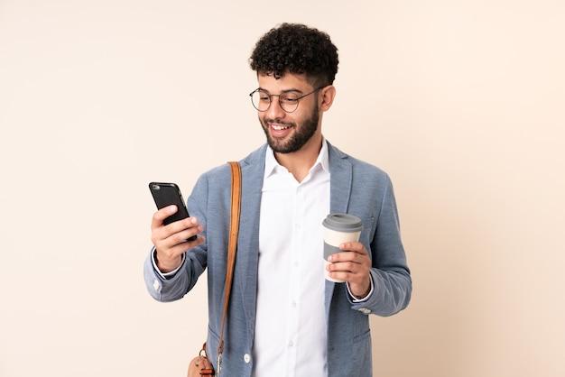 持ち帰り用のコーヒーと携帯電話を保持しているベージュの背景に分離された若いビジネスモロッコ人