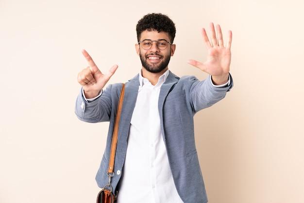 손가락으로 7 세 베이지 색에 고립 된 젊은 비즈니스 모로코 남자