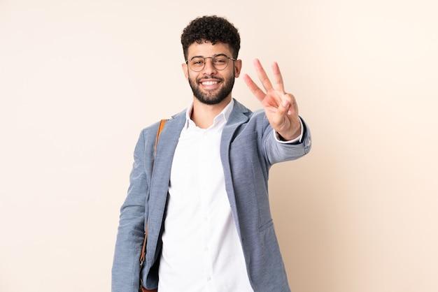 베이지 색 행복에 고립 된 젊은 비즈니스 모로코 남자 손가락으로 세 세