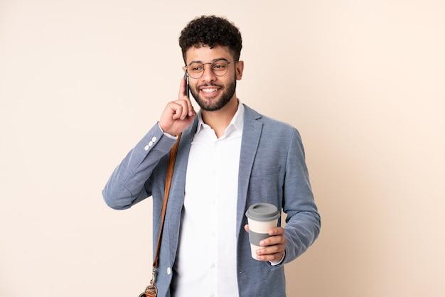 持ち帰り用のコーヒーと携帯電話を保持しているベージュに分離された若いビジネスモロッコ人
