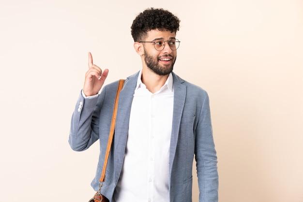 손가락을 들어 올리는 동안 솔루션을 실현하려는 베이지 색에 고립 된 젊은 비즈니스 모로코 남자