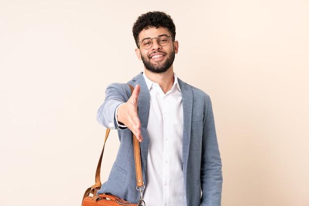 좋은 거래를 닫기 위해 악수하는 베이지 색에 고립 된 젊은 비즈니스 모로코 남자