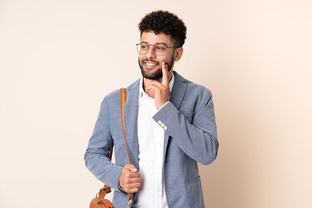찾는 동안 아이디어를 생각하는 베이지 색에 고립 된 젊은 비즈니스 모로코 남자