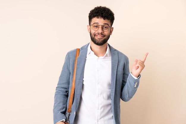 검지 손가락으로 좋은 아이디어를 가리키는 베이지 색 벽에 고립 된 젊은 비즈니스 모로코 남자