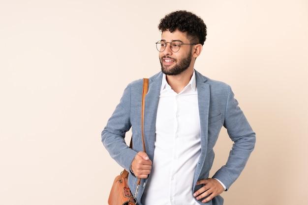 엉덩이에 팔을 포즈와 미소 베이지 색 벽에 고립 된 젊은 비즈니스 모로코 남자