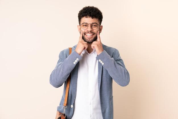 Молодой деловой марокканский мужчина изолирован на бежевой стене, улыбаясь счастливым и приятным выражением лица