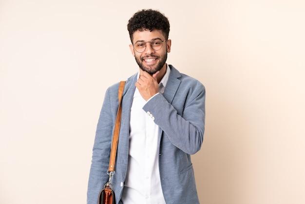 眼鏡と笑顔でベージュの壁に分離された若いビジネスモロッコ人