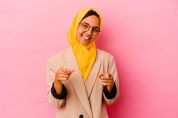 ピンクの背景に分離された若いビジネスイスラム教徒の女性は、正面を指している陽気な笑顔。