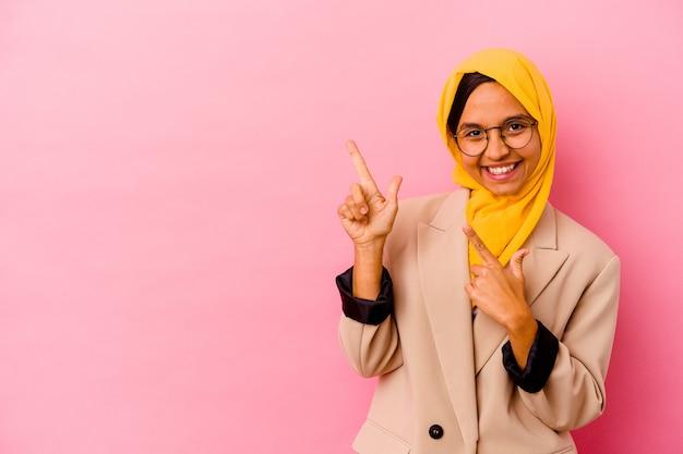 ピンクの背景に孤立した若いビジネスイスラム教徒の女性は、興奮と欲望を表現し、コピースペースに人差し指で指しています。
